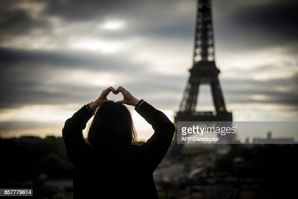 A tourist poses for a picture at sunrise in front of the eiffel tower on October 5 2017 in Paris / AFP PHOTO / Lionel BONAVENTURE