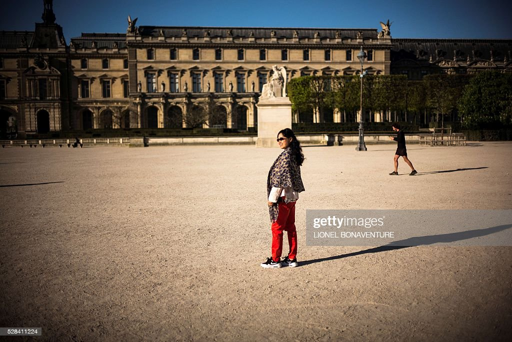 A tourist poses for a picture at the Tuileries garden on May 5, 2016 in Paris. / AFP / LIONEL