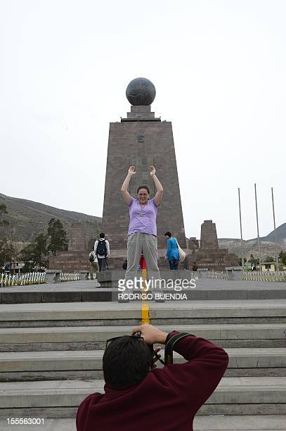 A tourist poses for a picture in front of the 'Middle of the world' monument in Quito Ecuador on November 5 2012 The world's tallest tower 16 km...