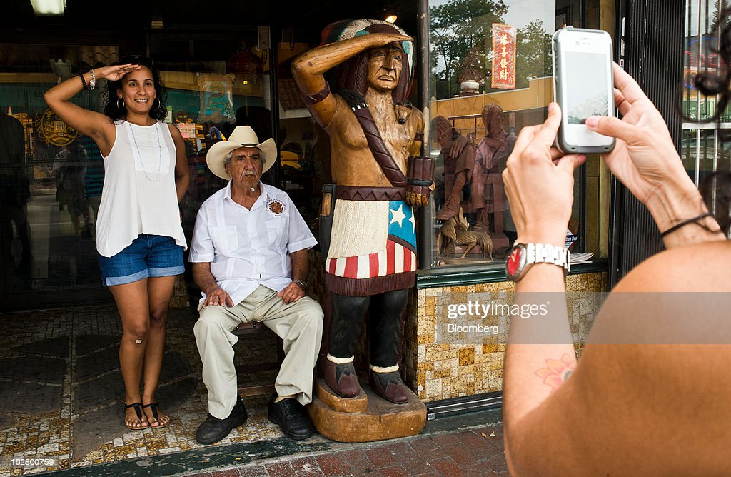 A tourist poses for a picture with a man smoking a cigar in front of a shop on Calle 8, or Eighth Street, in the Little Havana district of Miami, Florida, U.S., on Wednesday, Feb. 20, 2013. U.S. exports in the travel and tourism sector reached $168.1 billion in 2012, up 10.1 percent from the year-ago level of $152.7 billion, according to data released Feb. 22 by the Commerce Department's International Trade Administration. Photographer: Ty Wright/Bloomberg via Getty Images