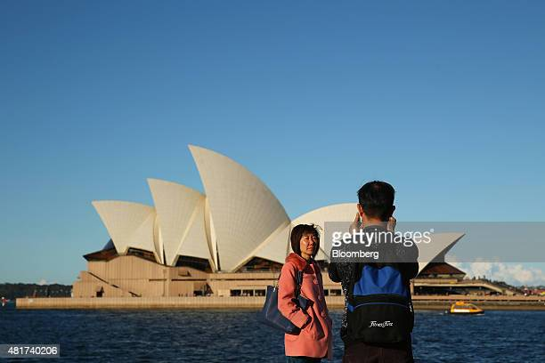 A tourist poses for photographs in front of the Sydney Opera House in Sydney Australia on Tuesday July 21 2015 Tired hotels outdated attractions like...