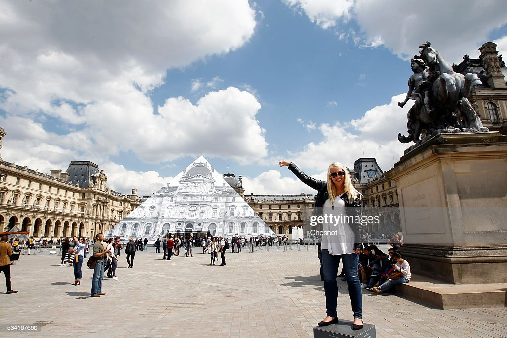 A tourist poses in front of the artwork of French street artist and photographer JR displayed on the Louvre Pyramid on May 25, 2016 in Paris France. French street artist JR has installed a huge photographic collage on the Louvre pyramid for making it disappear and creating a giant optical illusion through an anamorphosis, a technique that allows to appear or disappear a work.