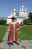 The tourist poses in historical clothes in Rostov Kremlin, Russia