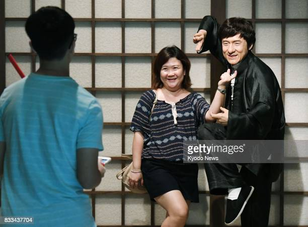 A tourist poses next to a wax doll of Hong Kong martial artist and actor Jackie Chan in Hong Kong in June 2017 ==Kyodo