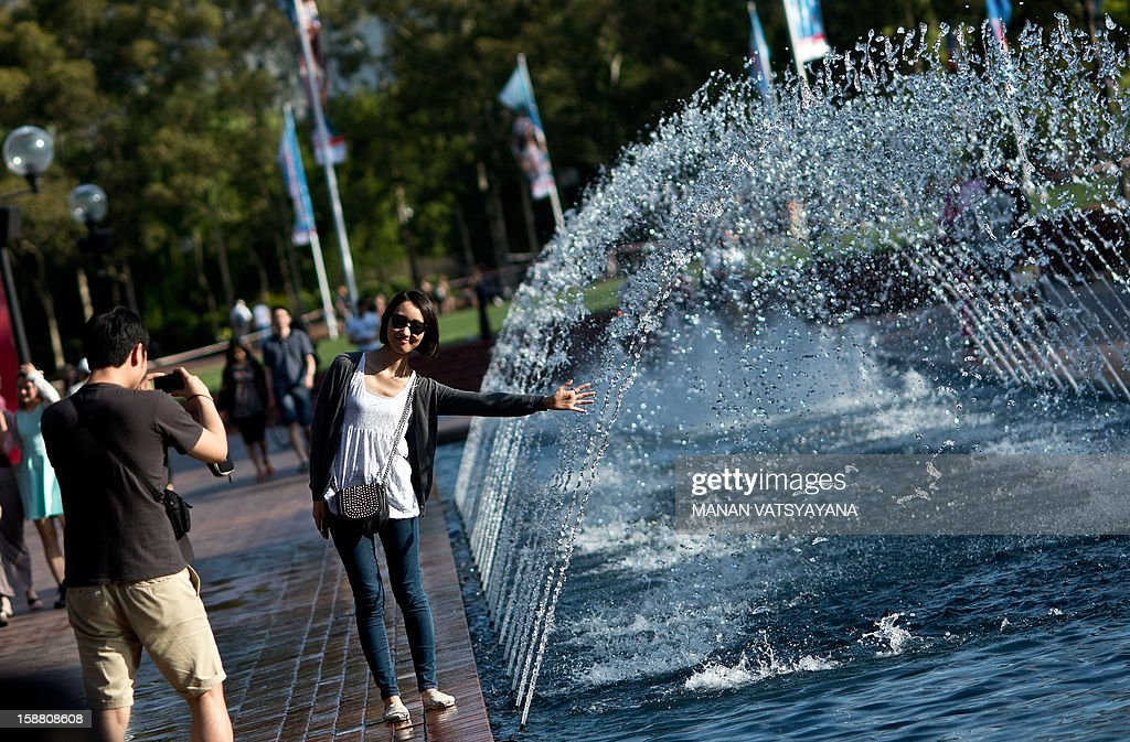 A tourist poses next to fountains near Tumbalong Park in Sydney's Darling Harbour area on December 30, 2012. International visitors to Australia are expected to increase from over 5.9 million in 2010-11 to nearly 8.2 million in 2020-21, an average annual growth rate of three percent, reported Tourism Research Australia (TRA).