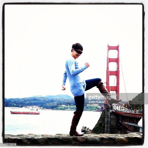 A tourist poses while having her picture taken near the Golden Gate Bridge on May 3 2012 in Sausalito California The Golden Gate Bridge Highway and...