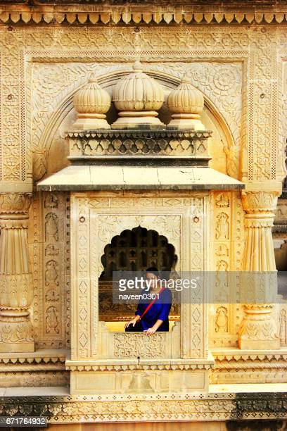 Tourist posing in a window in Ahilya fort in Maheshwar, India