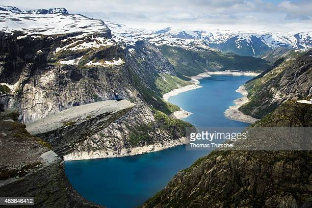 Tourist posing on the rocky tip of the natural monument Trolltunga2015 in Hardangervidda close to Tyssedal in the province Hordaland in Norway on...