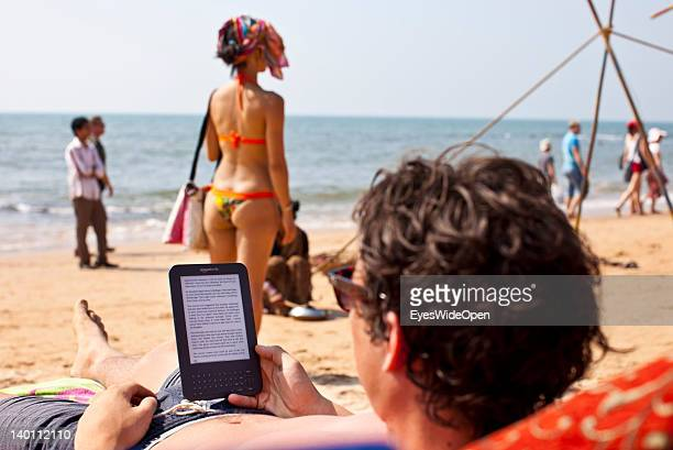 A tourist reads a book with an amazon ereader kindle at the sandy beach of Anjuna on February 1 2012 in Goa India