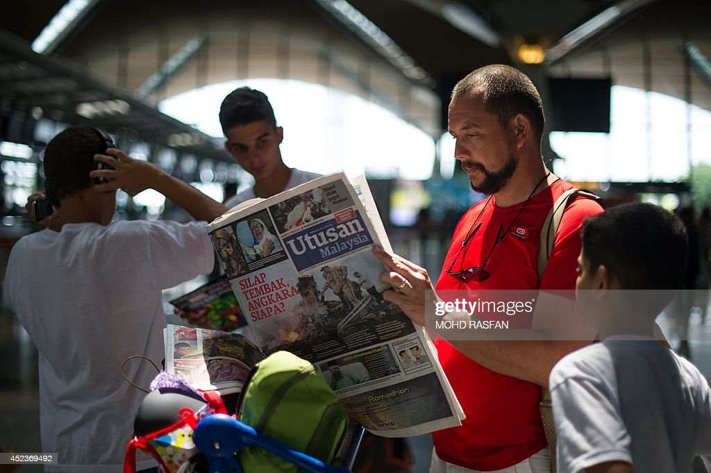 A tourist reads a Malaysian newspaper with reports about the Malaysia Airlines flight MH17 that crashed in eastern Ukraine, at Kuala Lumpur International Airport in Sepang, on July 19, 2014. Malaysia Airlines Flight MH17 carrying 298 people from Amsterdam to Kuala Lumpur crashed on July 17 in rebel-held east Ukraine, as Kiev said the jet was shot down in a 'terrorist' attack.
