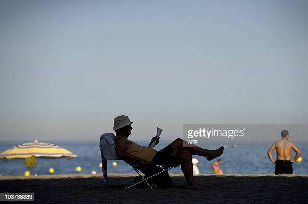 A tourist reads at the Carihuela beach in Torremolinos southern Spain on August 3 2009 Spain is feeling the pinch of a drop in visitors especially...