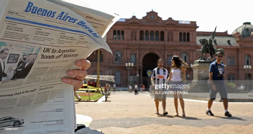 A tourist reads the Buenos Aires Herald in which Britain's biggest-selling tabloid The Sun placed an advert warning Argentina to keep its 'hands off' the Falklands, in front of the presidential palace Casa Rosada in Buenos Aires, on January 4, 2013. The Sun hit back at Argentina's President Cristina Fernandez de Kirchner's renewed claim over the disputed Falkland Islands in an open letter to her in the Buenos Aires Herald newspaper on Friday, a day after Fernandez de Kirchner published her own open letter in two British newspapers urging Britain to give up the South Atlantic islands. AFP PHOTO/ALEJANDRO PAGNI