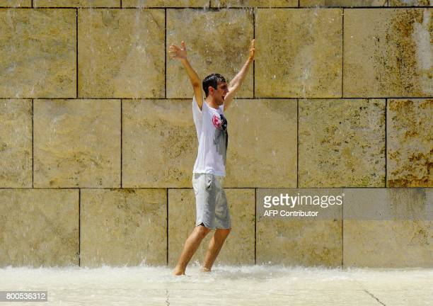 A tourist refreshes himself in a fountain in Rome on June 24 2017 In Italy forecasters say the current heatwave could turn out to be the most intense...