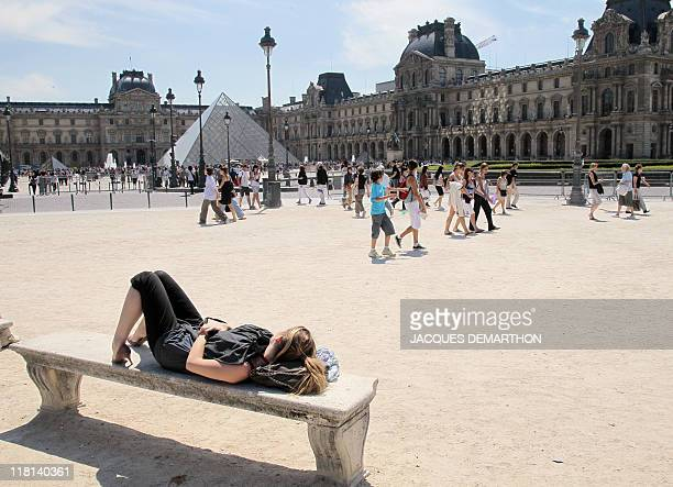 A tourist rests on a bench at the Carrousel square in front of the Louvre Museum buildings on July 42011 in Paris According to French Tourism...