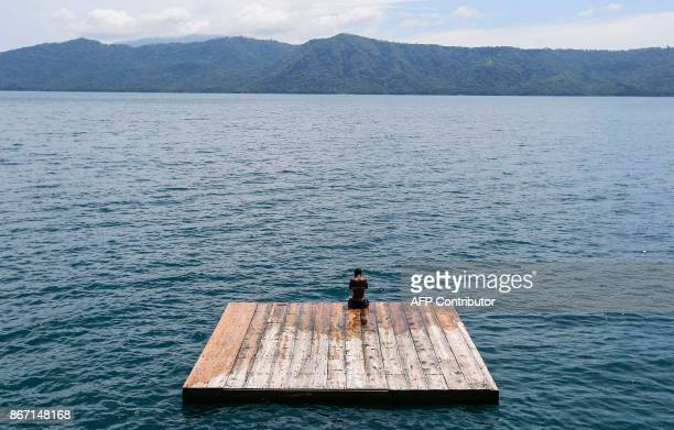 TOPSHOT A tourist rests on a floating dock at the 'Laguna de Apoyo' volcanic lagoon in Granada about 43 kilometres from Managua on October 14 2017...