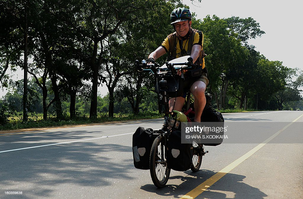 A tourist rides a bicycle in Madawachchiya on January 29, 2013. The number of foreign tourists visiting Sri Lanka has swelled since the island ended a 37-year separatist conflict with Tamil Tiger rebels in May 2009. AFP PHOTO/ Ishara S