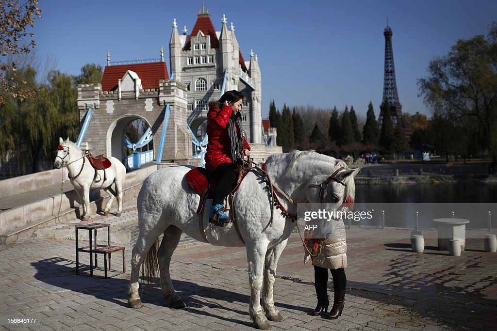 A tourist rides a horse before the mini replicas of London Bridge and the Effiel Tower in Beijing World Park, in the southwestern suburb of Beijing on November 23, 2012. Beijing World Park, with a collection of mini replicas of famous architectures from all over the wolrd, attempts to give visitors a chance to see the world without having to leave Beijing. CHINA OUT AFP PHOTO
