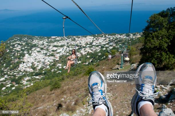 A tourist rides down the Monte Solaro chair lift from the highest point of Capri, Italy
