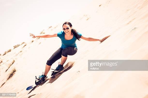 tourist sandboarding in the desert