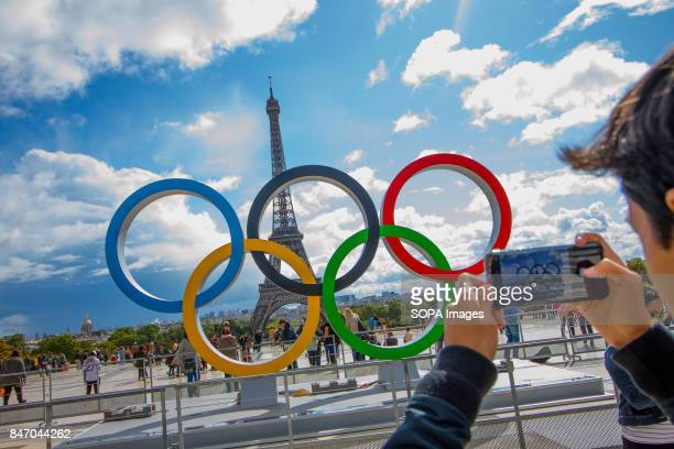 A tourist seen taken picture of the Olympic Rings with his mobile phone The Olympic Rings being placed in front of the Eiffel Tower in celebration of...