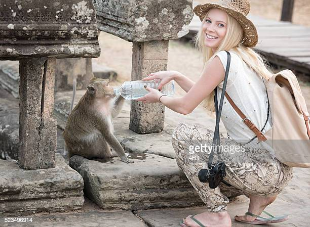 Tourist sharing her Water with a Monkey at Angkor Wat
