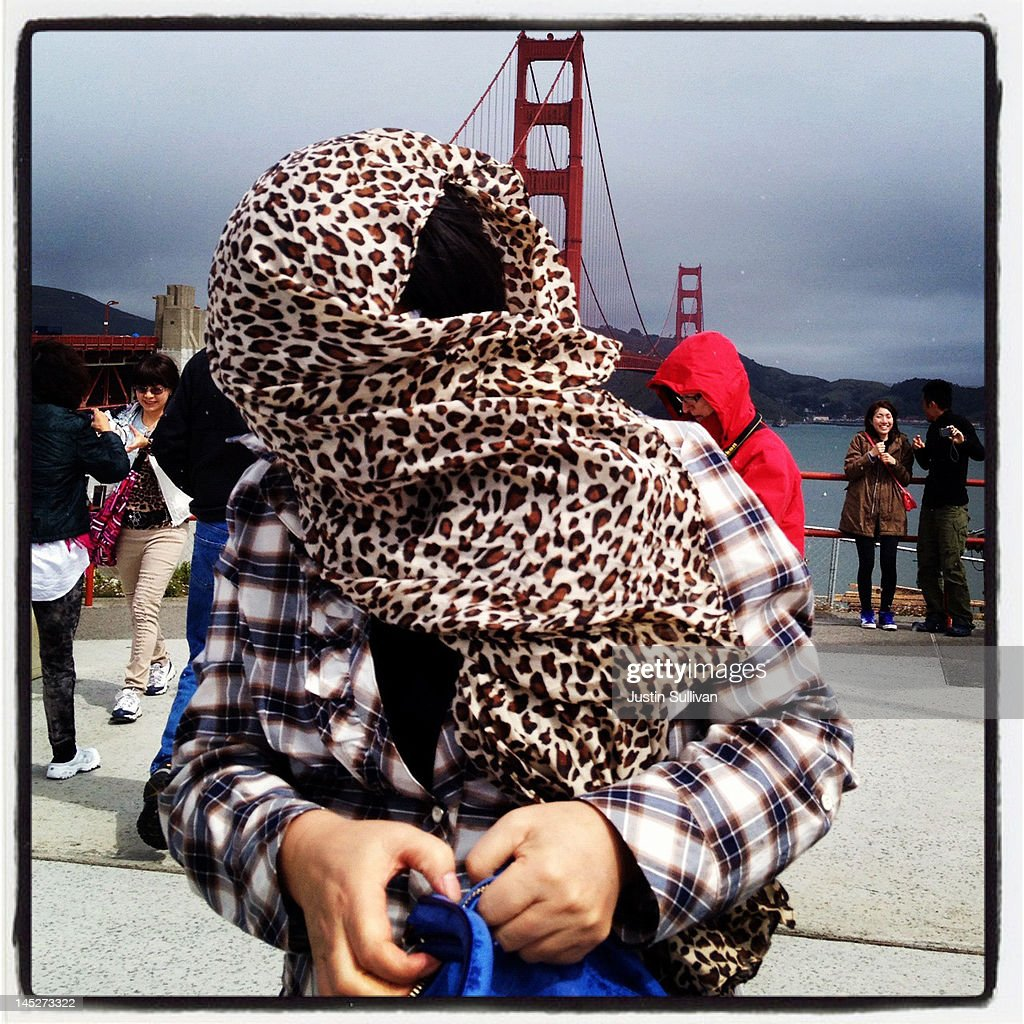 A tourist shields herself from a light rain as she walks near the Golden Gate Bridge on May 3, 2012 in San Francisco, California. The Golden Gate Bridge, Highway and Transportation District is preparing for the 75th anniversary of the iconic Golden Gate Bridge that will be marked with a festival on May 26 - 27 that will feature music, displays of bridge artifacts and art exhibits. The 1.7 mile steel suspension bridge, one of the modern Wonders of the World, opened to traffic on May 27, 1937.