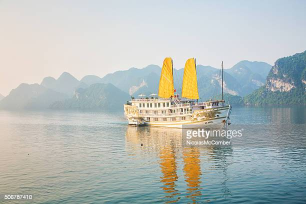Tourist ship with sails cruising on Halong Bay Vietnam