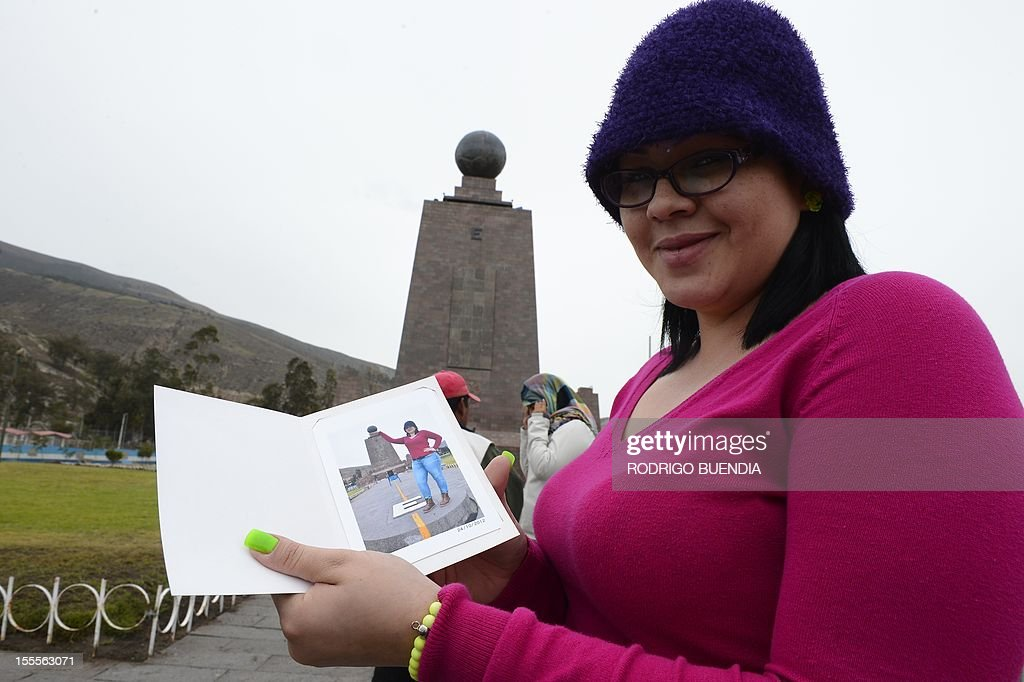 A tourist shows a picture of herself in front of the 'Middle of the world' monument, in Quito, Ecuador, on November 5, 2012. The world's tallest tower, 1.6 km, could be erected in Ecuador on the imaginary line that divides the world into two, a budding mega-project to honor the indigenous past and boost tourism, and it would take the mark of the Uruguayan architect Rafael Vinoly.