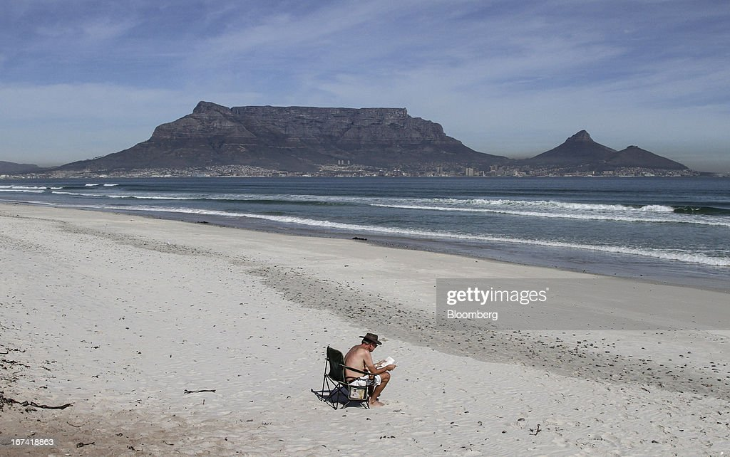 A tourist sits and reads at the seaside on Table Bay beach with a view of Table Mountain, center, in Cape Town, South Africa, on Wednesday, April 24, 2013. South Africa's gross domestic product is forecast to expand 2.6 percent this year, compared with 2.5 percent in 2012, according to the country's central bank. Photographer: Nadine Hutton/Bloomberg via Getty Images