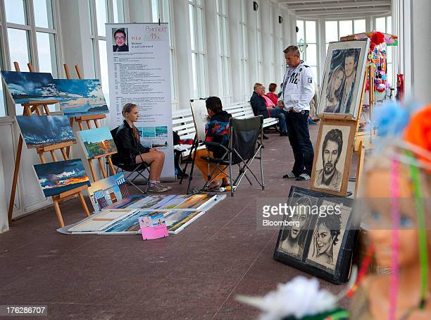 A tourist sits for a portrait by an artist in Binz on Ruegen Island Germany on Saturday Aug 10 2013 Chancellor Angela Merkel's drive to get more...