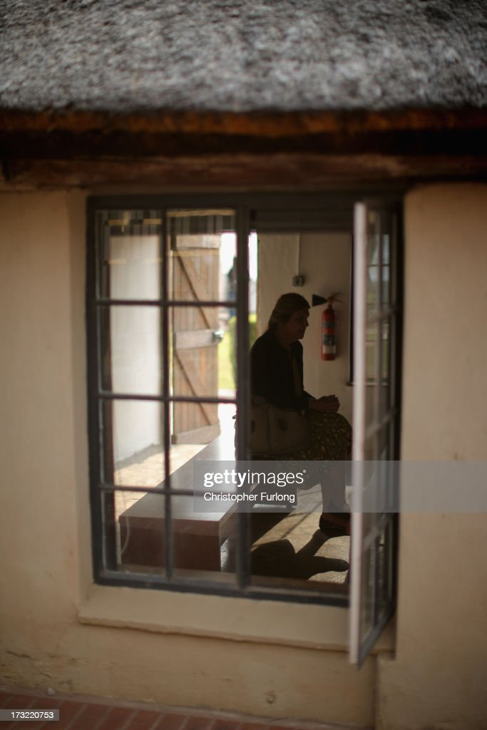 A tourist sits in the thatched cottage at Lilisleaf Farm where ANC freedom fighters held their Operation Mayibuye meeting 50 years ago. July 10, 2013 in Rivonia, South Africa. Tomorrow marks the 50th anniversary since the hideout was raided by police on 11th July 1963. The farm was the secret nerve centre for the ANC underground and the police interrupted a meeting of Operation Mayibuye, a plan to overthrow the Apartheid government. The raid by police led to the arrest of Nelson Mandela, Walter Sisulu, Ahmed Kathrada and Govan Mbeki, who were later convicted through the infamous Rivonia Trial and most were sentenced to life imprisonment on Robben Island.