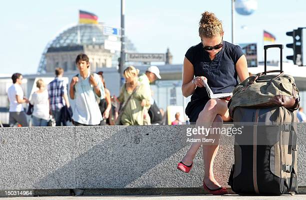 A tourist sits next to her suitcase in front of the Reichstag the seat of the German parliament on August 15 2012 in Berlin Germany In 2010 nine...