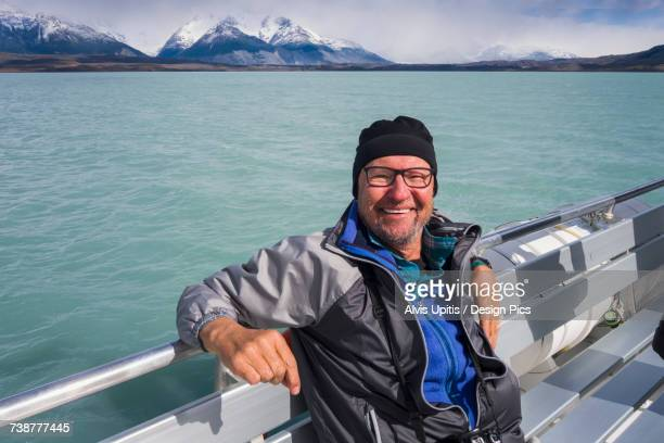 A tourist sits on a boat and poses for a picture on a cruise of Lake Argentino near El Calafate, Argentinian Patagonia