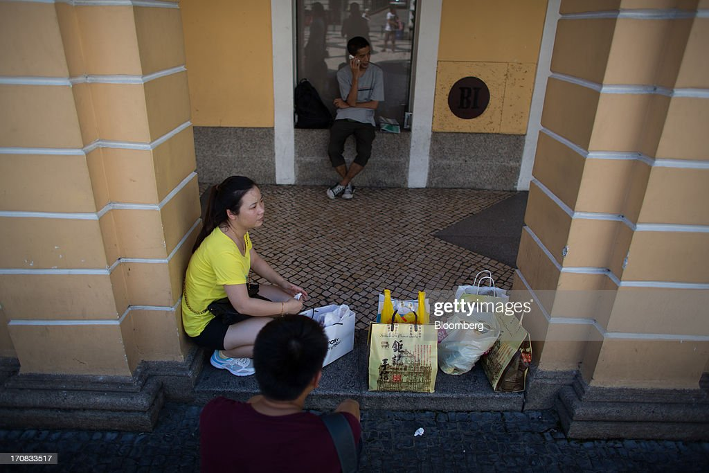 A tourist sits outside a store with shopping bags in the city center of Macau, China, on Tuesday, June 18, 2013. Casino revenue in Macau, the only place in China where casino gambling is legal, rose 14 percent to a record of 304 billion patacas ($38 billion) in 2012. Photographer: Lam Yik Fei/Bloomberg via Getty Images