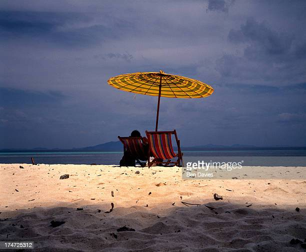A tourist sits under an umbrella in Maya Bay on Ko Phi Phi Famous for their palm fringed beaches dazzling white sands and limestone cliffs Ko Phi Phi...