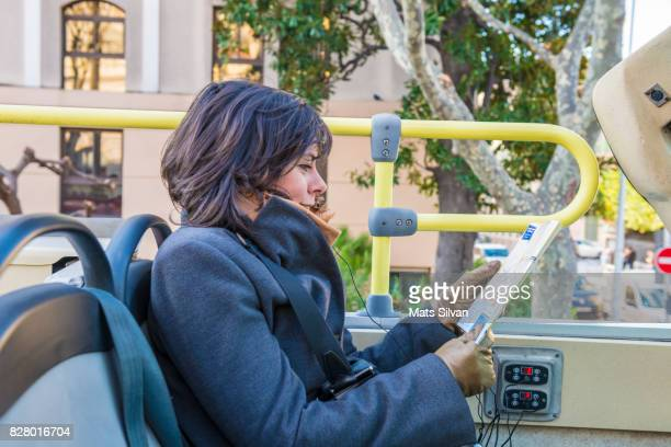 Tourist Sitting in a Bus with Headphones and Tourist Guide in Nice