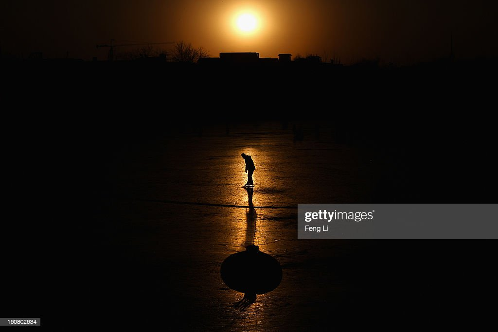A tourist skates on the frozen Houhai Lake during sunset on February 6, 2013 in Beijing, China.
