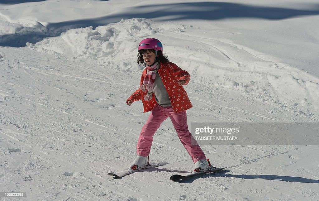 A tourist skis down a slope in Gulmarg, about 55 kms north of Srinagar, on December 31, 2012. Gulmarg is the main ski destination in Indian Kashmir and hundreds of foreigners visit the slopes despite an ongoing insurgency in the region. AFP PHOTO/ Tauseef MUSTAFA