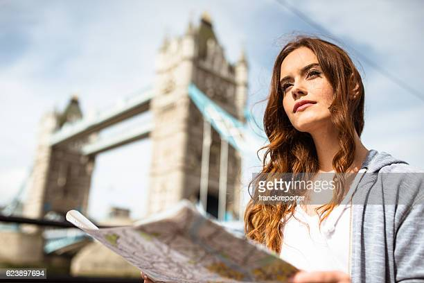 tourist smiling in London reading the map under