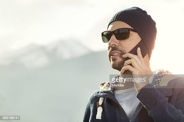 Turista hablando por teléfono en la montañas