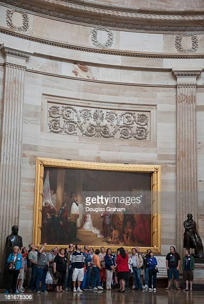 Tourist stand in front of the painting known as the 'Baptism of Pocahontas' in the US Capitol Rotunda on September 23 2013 The painting depicts the...