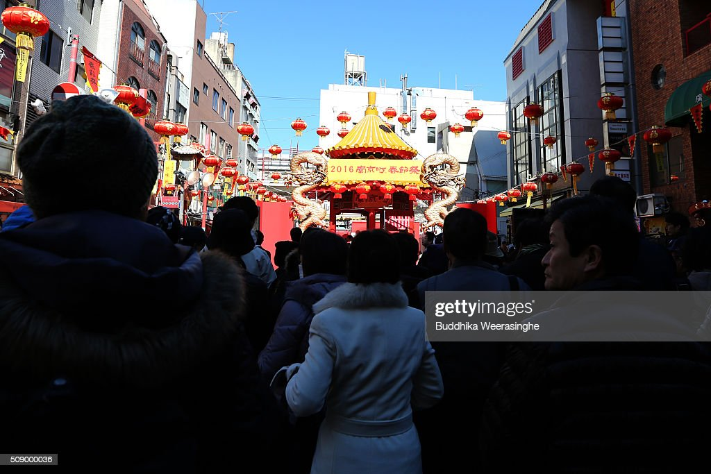 Tourist stand in the Nankinmachi square during the religious ritual to celebrate the Chinese New Year on a stage at the China Town on February 8, 2016 in Kobe, Japan. In Nankinmachi, the district known as Kobe Chinatown, tourists enjoyed Chinese food, lion dance and the parade organized to celebrate the Lunar New Year.