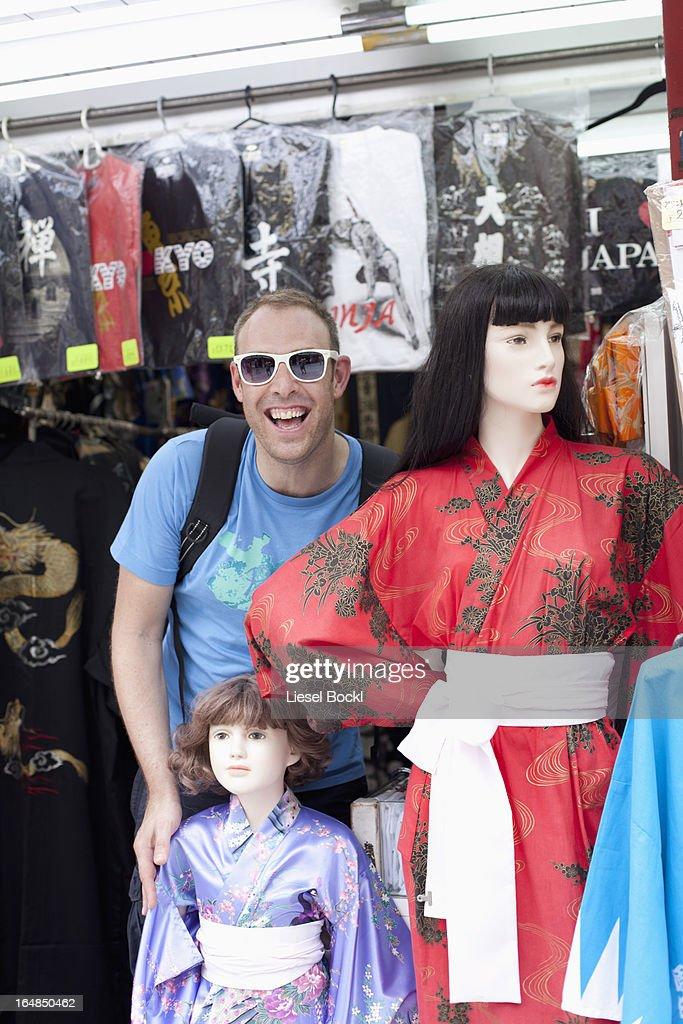 Tourist standing beside female mannequins wearing kimonos,