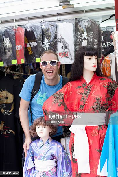 Tourist standing beside female mannequins wearing kimonos,