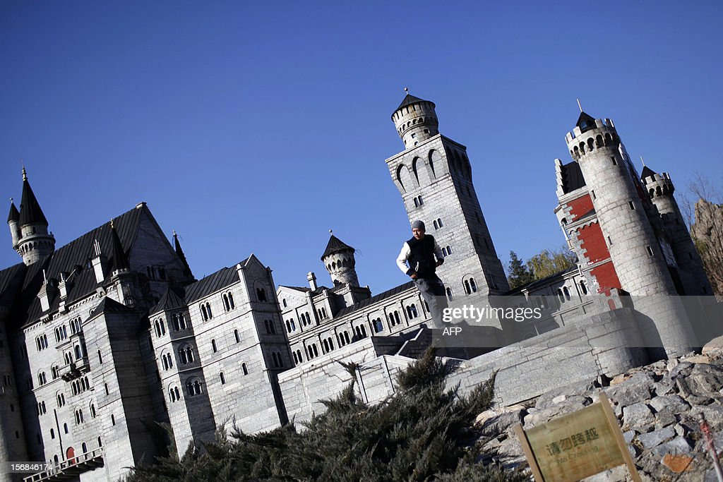 A tourist stands among a group of castles in Beijing World Park, in the southwestern suburb of Beijing on November 23, 2012. Beijing World Park, with a collection of mini replicas of famous architectures from all over the wolrd, attempts to give visitors a chance to see the world without having to leave Beijing. CHINA