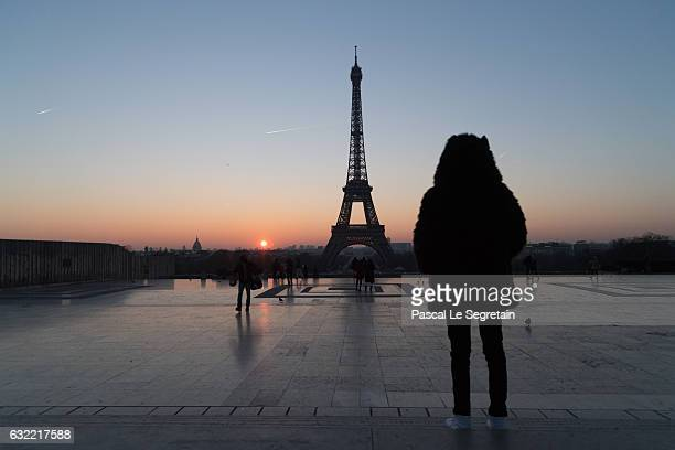 A tourist stands in front of the Eiffel tower at sunrise on January 18 2017 in Paris France