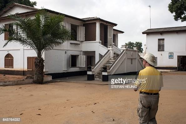 A tourist stands in front of the Museum of History on January 11 2017 in the small coastal town of Ouidah some 40km from Benin's capital Cotonou With...