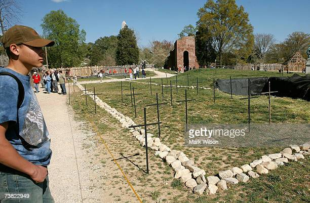 A tourist stands near twentytwo crosses that mark spots where archaeologists with the Association for the Preservation of Virginia Antiquities have...