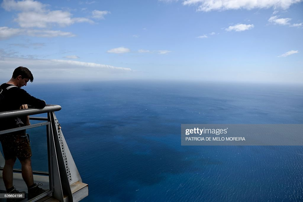 A tourist stands on a lookout on top of a cliff of Cabo Girao in Camara de Lobos, Madeira island on April 30, 2016. / AFP / PATRICIA