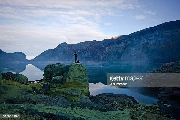 A tourist stands on a rock watching the view of Ijen Crater during an annual offering ceremony on the Ijen volcano on December 17 2013 in Banyuwangi...